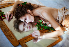 Curly sensual girl lying about a mirror, reflecting in it and ne. Ar red berry Stock Photos