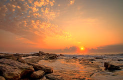 Curly sky sunrise seascape. This amazing sunrise occurred just after the sun broke through the clouds, transforming the sky, water and rocks into these Royalty Free Stock Photo