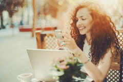 Curly smiling beautiful girl texting message in cafe Royalty Free Stock Image