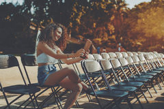 Curly smiling brunette girl making selfie on digital tablet. Curly brunette smiling beautiful girl on empty seat rows of folding chairs in park before concert Stock Photography