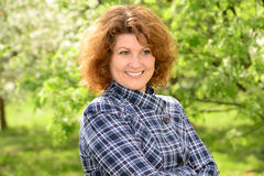 Curly smiling middle-aged woman outside royalty free stock photo