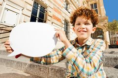 Curly teenage boy with white blanked speech bubble. Close-up portrait of cute curly teenage boy sitting on the steps outdoors with white blanked speech bubble royalty free stock photography
