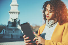 Curly thoughtful brunette woman with digital tablet. True tilt shift portrait of pensive curly woman with digital tablet on sunny street, thoughtful Brazilian Stock Images