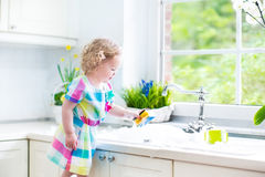 Curly toddler girl in colorful dress washing dishes. Cute curly toddler girl in a colorful dress washing dishes, cleaning with a sponge and playing with foam in stock image