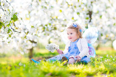 Curly toddler girl in fairy costume in fruit apple garden. Adorable toddler girl with curly hair and flower crown wearing a magic fairy costume with a blue dress Royalty Free Stock Image