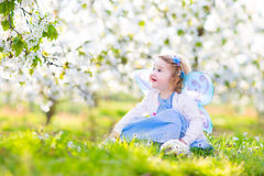 Curly toddler girl in fairy costume in fruit garden. Adorable toddler girl with curly hair and flower crown wearing a magic fairy costume with a blue dress and Royalty Free Stock Image