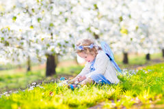 Curly toddler girl in fairy costume in fruit garden Stock Photos