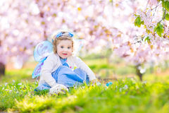 Curly toddler girl in fairy costume in fruit garden. Adorable toddler girl with curly hair and flower crown wearing a magic fairy costume with a blue dress and Stock Photos