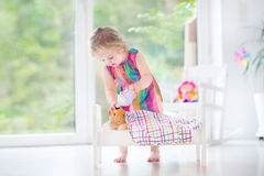 Curly toddler girl feeding her toy bear in white crib pla Royalty Free Stock Photography
