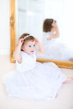 Curly toddler girl trying on white dress next mirror Royalty Free Stock Photography