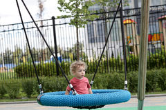 Curly toddler at swing Royalty Free Stock Images