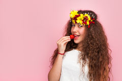 Curly woman biting strawberry royalty free stock photos