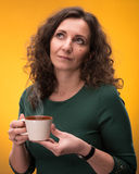 Curly woman with a cup of tea or coffee Royalty Free Stock Images