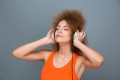 Curly woman with eyes closed in headphones listening to music. Pretty young curly woman with eyes closed in headphones listening music Royalty Free Stock Photo