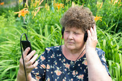 Curly woman listening to music with headphones and smartphone Royalty Free Stock Images
