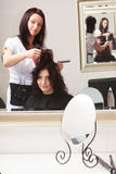 Curly woman looking at mirror by hairstylist. In hairdressing salon. Stock Photography