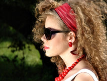 Curly woman with red jewellery Stock Photos