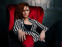 Curly woman siting on red chair Stock Photography