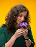Curly woman smelling crocus flowers with close eyes Stock Photography