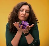 Curly woman smelling crocus flowers with close eyes Royalty Free Stock Photos