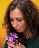 Curly woman smelling crocus flowers with close eyes Royalty Free Stock Image