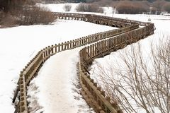 Curly wooden bridge over the frozen lake Stock Photos