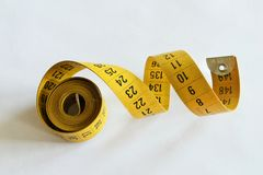 Curly yellow tape measure isolated. Yellow vintage measuring tape or body measuring ruler isolated on white background royalty free stock photo