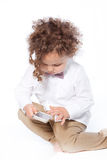 Curly Young Boy Swiping Mobile Phone Stock Image