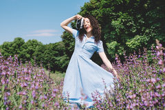 Curly young brunette in a blue dress with an old camer Royalty Free Stock Photos