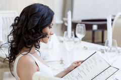 Curly young brunette choosing dishes from menu Royalty Free Stock Photo
