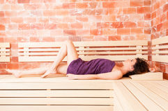Curly young female stretched out on wooden bench. Relaxing in sauna room Stock Image