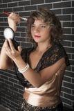 Curly young girl puts her makeup Stock Photos