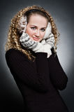 Curly young woman in furs earphone and mitten Stock Photos