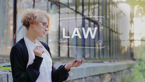 Blonde uses hologram Law. Curly young woman in glasses interacts with a hud hologram with text Law. Blonde girl in white and black clothes uses technology of the stock footage