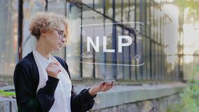 Blonde uses hologram NLP. Curly young woman in glasses interacts with a hud hologram with text NLP. Blonde girl in white and black clothes uses technology of the stock video