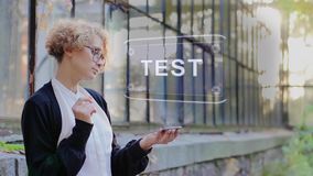 Blonde uses hologram Test. Curly young woman in glasses interacts with a hud hologram with text Test. Blonde girl in white and black clothes uses technology of stock video