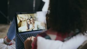 Curly young woman having video chat with friends using laptop camera while lying on bed. At home stock footage