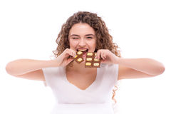 Curly young woman with plate of  milk chocolate at table. Royalty Free Stock Photo