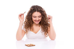 Curly young woman with plate of  milk chocolate at table. Stock Photos