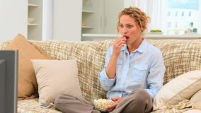 Curlyhaired lady watching the tv Royalty Free Stock Photo