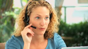 Curlyhaired woman speaking over the headset Stock Photography