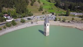 Curon, Italy. Drone aerial view of the old bell tower of the village rising out of the waters lake of Resia stock video footage