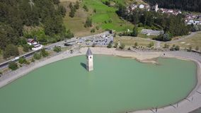 Curon, Italy. Drone aerial view of the old bell tower of the village rising out of the waters lake of Resia stock video