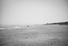 Curonian Spit, Figures on Baltic Sea. At the beach in the morning, two peoples walk near Nida Stock Image