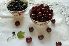 Currant berries and cherries on a white plate and white tablecloth Stock Photo