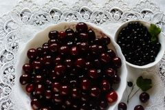 Currant berries and cherries on a white plate and white tablecloth Stock Image