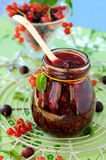 Currant jam. A glass jar with currant jam and a ceramic spoon royalty free stock photos