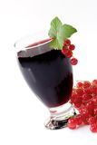 Currant Juice. A glass of black currant juice with garnish on light background royalty free stock photography