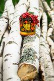 Birch logs and decorative wooden pot in Khokhloma style, overfilled by bunches of ripe red currant. The currant is one of the most widespread berry shrubs of Royalty Free Stock Photography