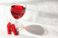 Currant wine. Wine made from red currants in a wine glass with some fruits Stock Photos